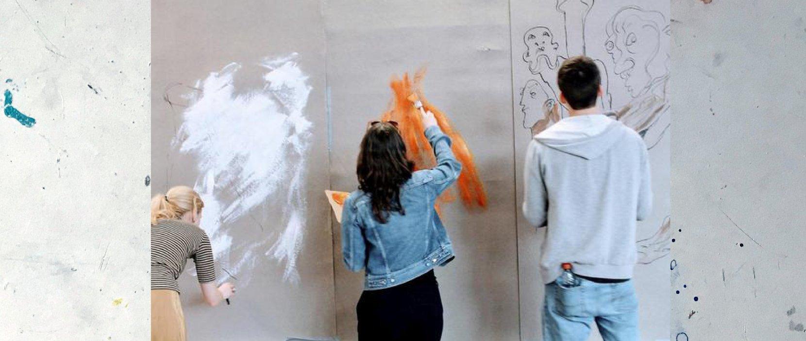 foto af tre unge der maler på en væg
